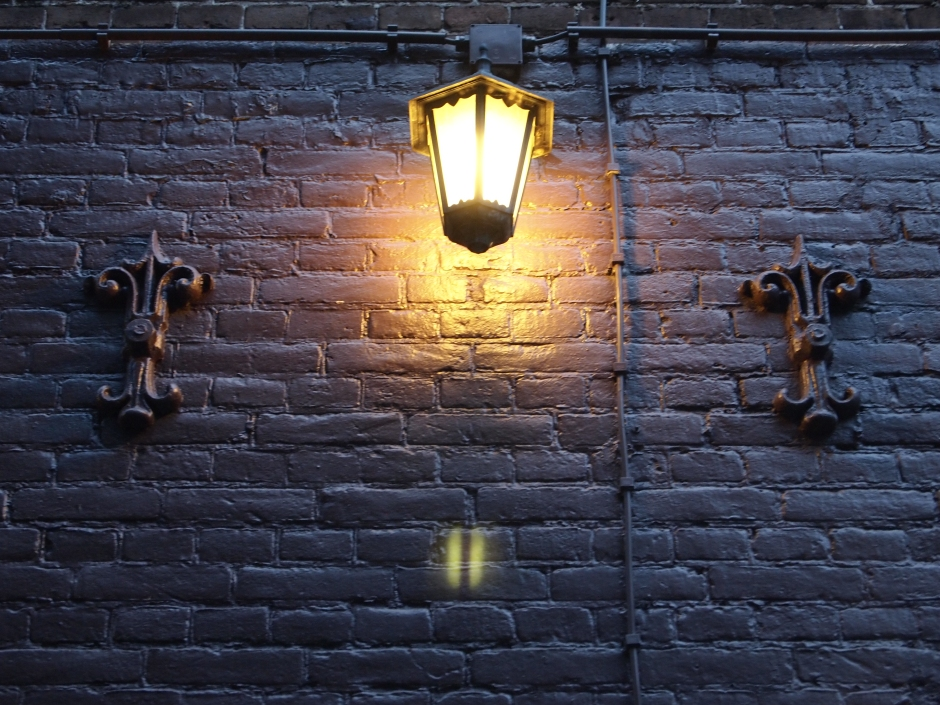 A lantern lights up a dark wall.